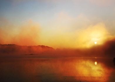 The sun rises through mist over a lake in the Appalachi ...