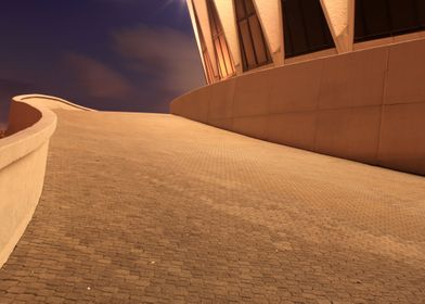 A night shot on a ramp leading to a coliseum.