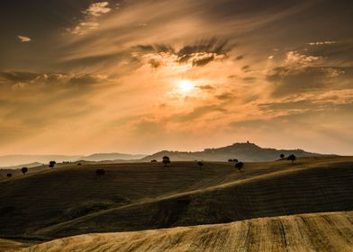 Wheat fields hills at sunrise with historic village of  ...