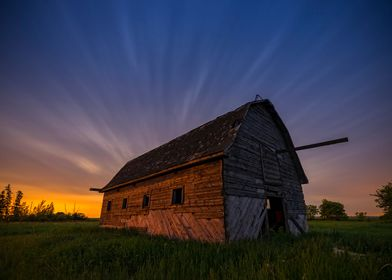 Abandoned barn at night with moving clouds and city lig ...