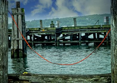 Red Rope - A red rope tied between two posts at docksid ...