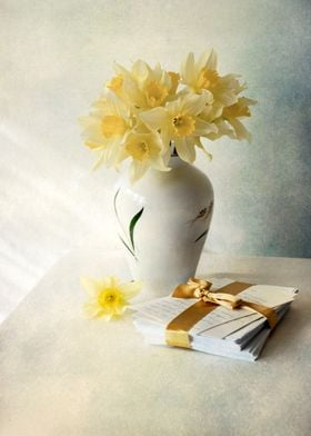 Still life with daffodils in the vase and pile of lette ...
