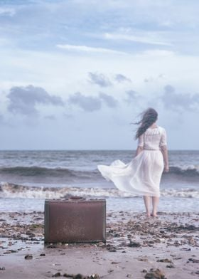 a woman is walking into the sea, leaving her luggage be ...
