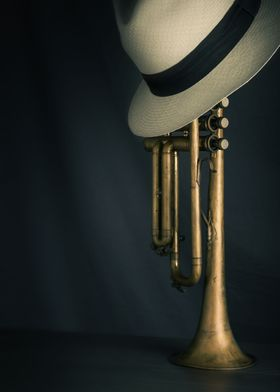 Vertically standing trumpet with fedora hat on top over ...