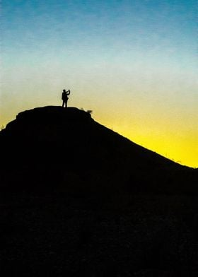 A photographer stands silhouetted on a hill as the dese ...